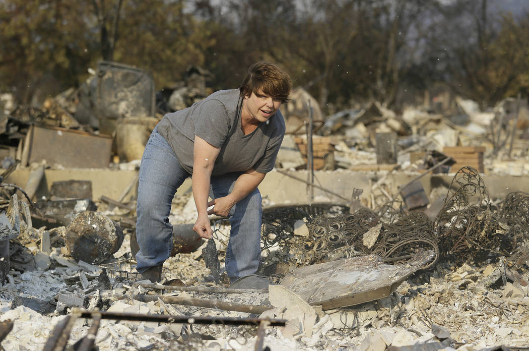 Tammy Christiansen searches the remains of her Coffey Park neighborhood home Wednesday, Oct. 11, 2017, in Santa Rosa, Calif. During her search she found her wedding ring and her son's wrestling tr ...