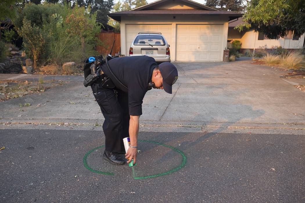 Oakland Police officer Anh Nguyen spray paints the street to mark that a house in Calistoga, Calif., is vacant on Wednesday, Oct. 11, 2017. The entire historic town of Calistoga, population 5,000, ...