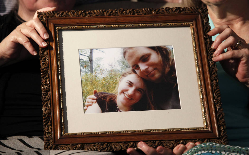 Mothers Linda Boyle, left and Lyn Coleman hold photo of their married children, Canadian citizen Joshua Boyle and American citizen Caitlan Coleman on June 4, 2014. (AP Photo/Bill Gorman, File)