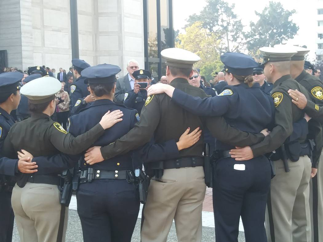 San Francisco and Las Vegas police officers share hugs on Thursday, Oct. 12, 2017, after the funeral Mass for Stacee Etcheber. Etcheber was one of the 58 victims of the Las Vegas shooting on Oct.  ...