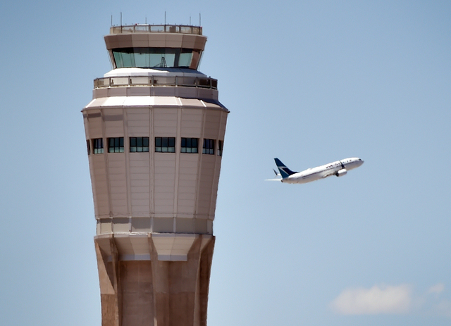 A jet airliner gains altitude by the air traffic control tower after taking off from McCarran International Airport. (David Becker/Las Vegas Review-Journal)