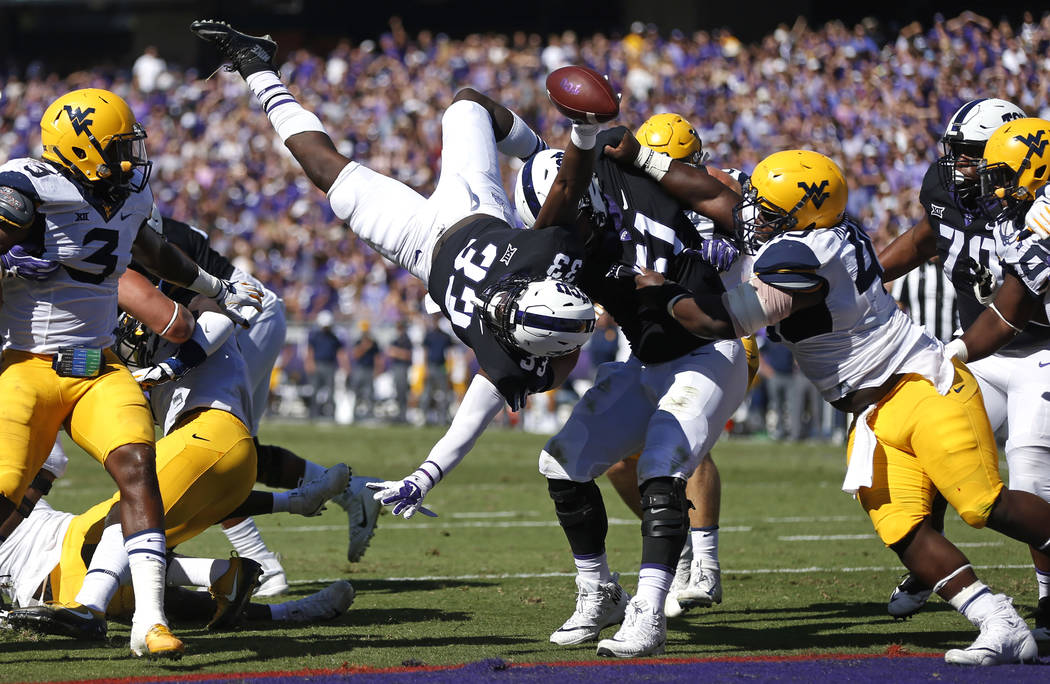 TCU running back Sewo Olonilua (33) dives over the goal line to score a touchdown against West Virginia during the second quarter of an NCAA college football game Saturday, Oct. 7, 2017, in Fort W ...