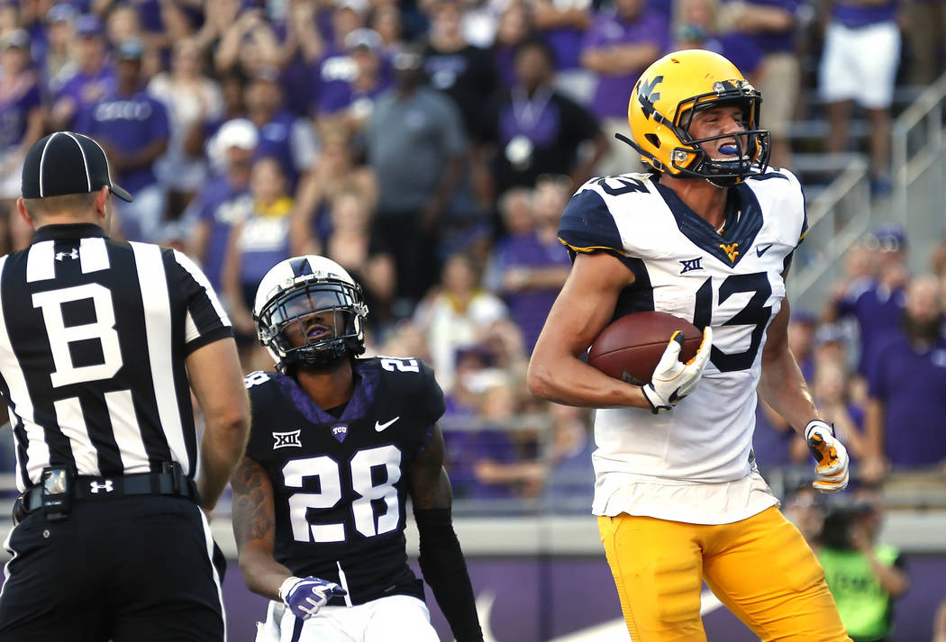 West Virginia wide receiver David Sills V (13) scores on a touchdown pass as TCU cornerback Tony James (28) looks on during the second half of an NCAA college football game Saturday, Oct. 7, 2017, ...