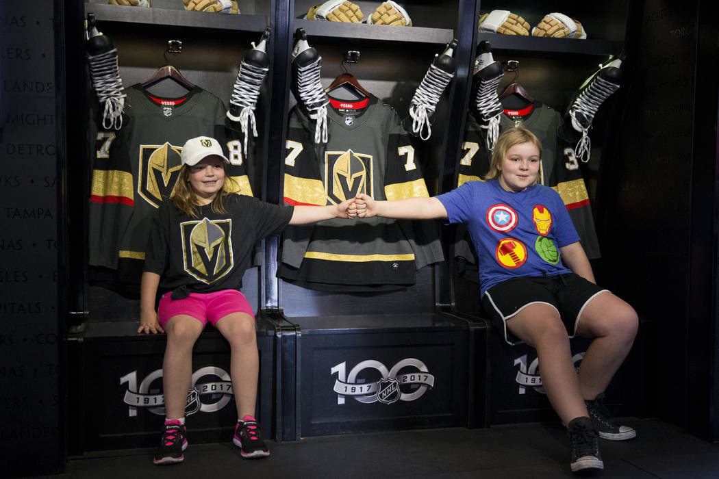 Adyson DeGraw, left, 9, and her sister Emma, 12, of Las Vegas, take a picture inside the Mobile NHL Museum in the NHL Centennial Fan Arena at the Fremont Street Experience in Las Vegas, Saturday,  ...