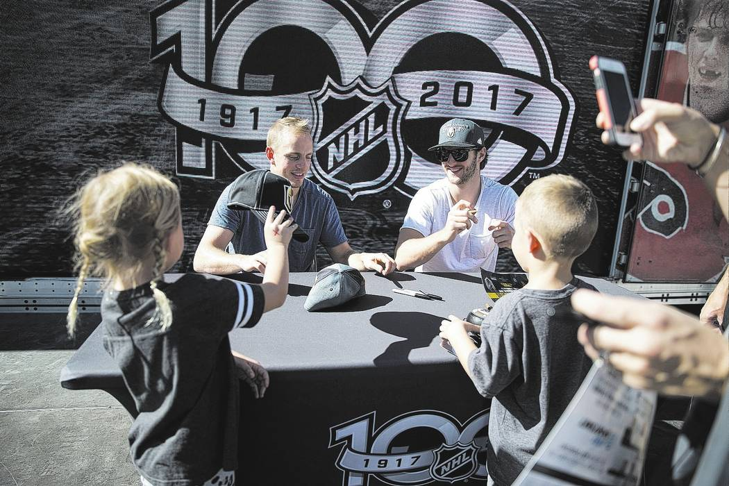 Vegas Golden Knights players Nate Schmidt, left, and Colin Miller sign autographs in the NHL Centennial Fan Arena at the Fremont Street Experience in Las Vegas, Saturday, Oct. 14, 2017. Erik Verdu ...