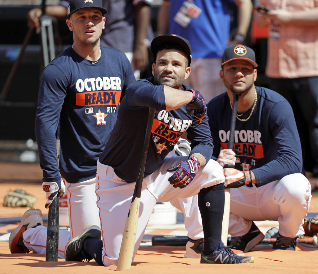 Houston Astros second baseman Jose Altuve, center, waits to bat with third baseman Alex Bregman, left, and first baseman Yuli Gurriel during baseball practice Wednesday, Oct. 11, 2017, in Houston. ...