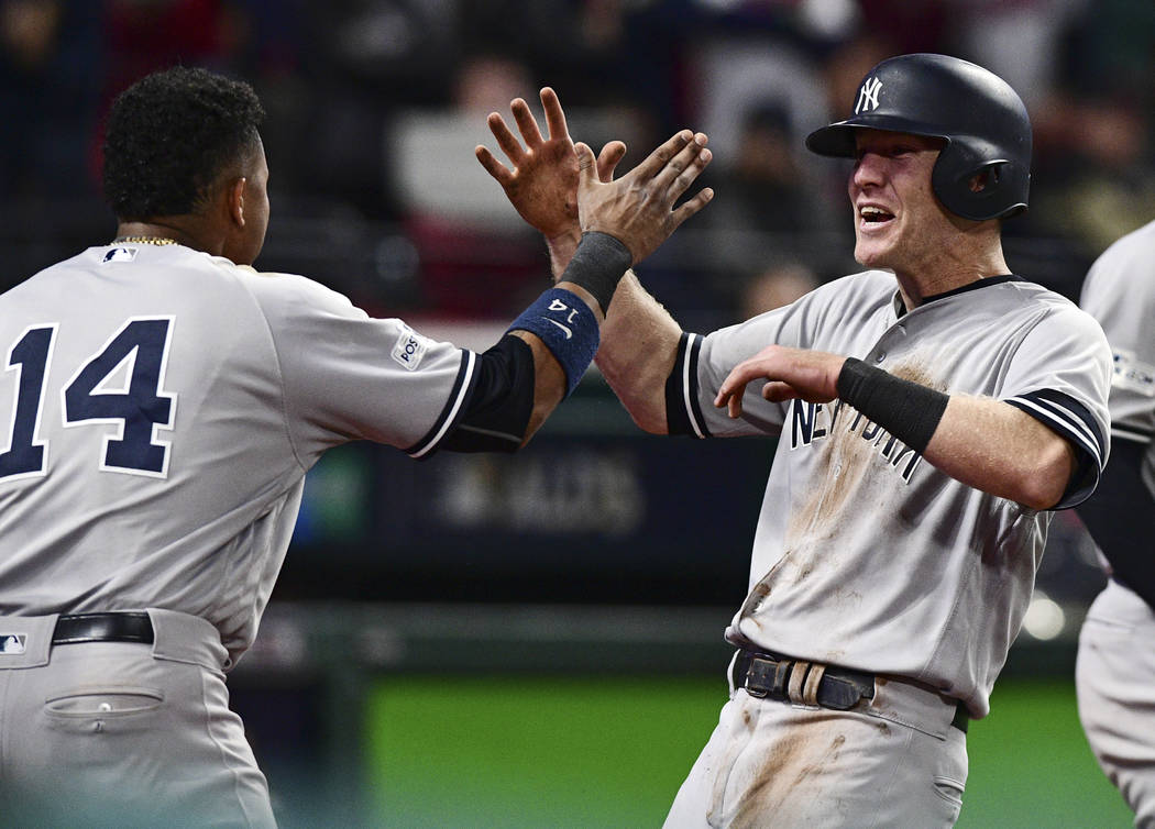 New York Yankees' Todd Frazier, right, celebrates with Starlin Castro after Frazier scored in the ninth inning of Game 5 of baseball's American League Division Series against the Cleveland Indians ...