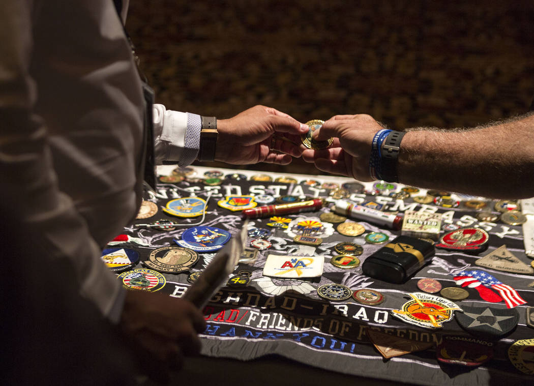 "Individuals look at a veteran medal during the MGM Resorts International annual ""Salute to the Troops"" event for ""wounded warriors,"" at The Mirage hotel-casino in Las Vegas, Oct. 12, 2017. Elizabe ..."