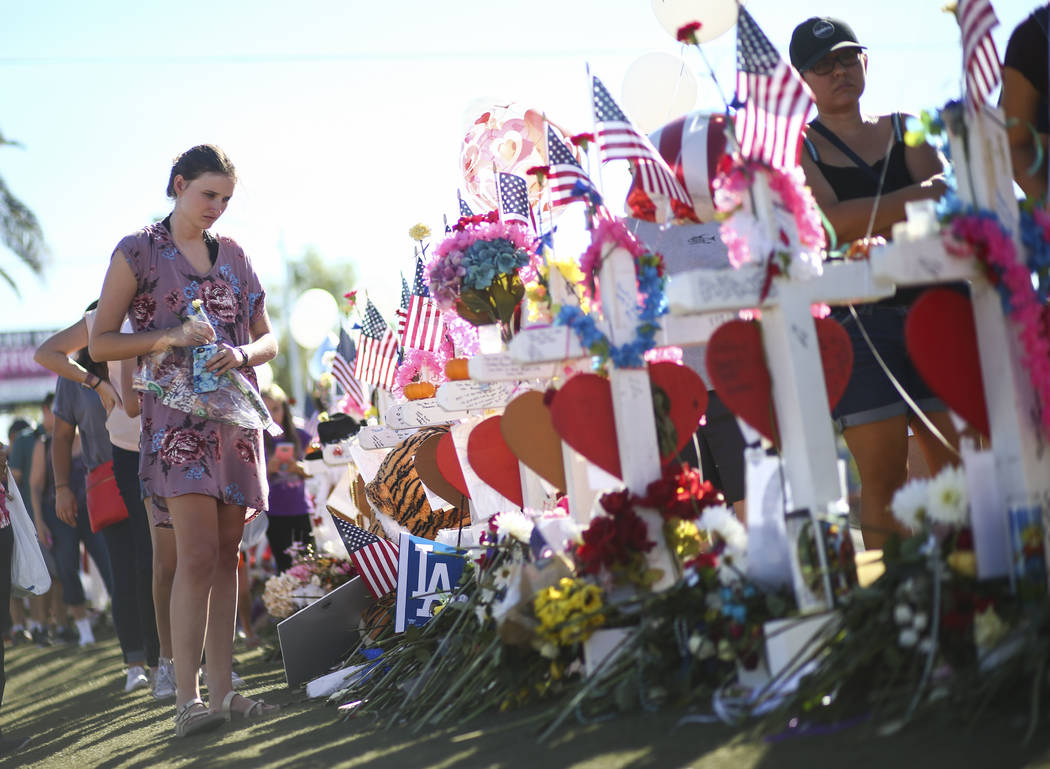 """Kylie Wright of Flagstaff, Ariz. leaves behind roses at a makeshift memorial for victims of the mass shooting near the """"Welcome to Fabulous Las Vegas"""" sign in Las Vegas on Saturday, Oct. 7, 2017.  ..."""