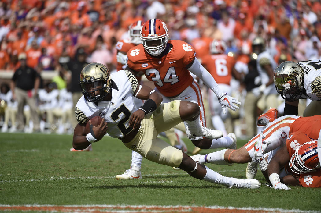 Wake Forest quarterback Kendall Hinton (2) is tackled by Clemson players during the first half of an NCAA college football game, Saturday, Oct. 7, 2017, in Clemson, S.C. Clemson won 28-14. (AP Pho ...