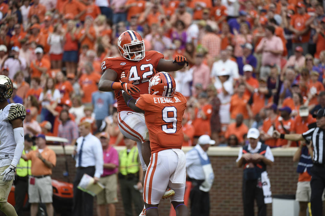 Clemson running back Travis Etienne (9) celebrates his touchdown with teammate Christian Wilkins during the second of an NCAA college football game against Wake Forest, Saturday, Oct. 7, 2017, in  ...