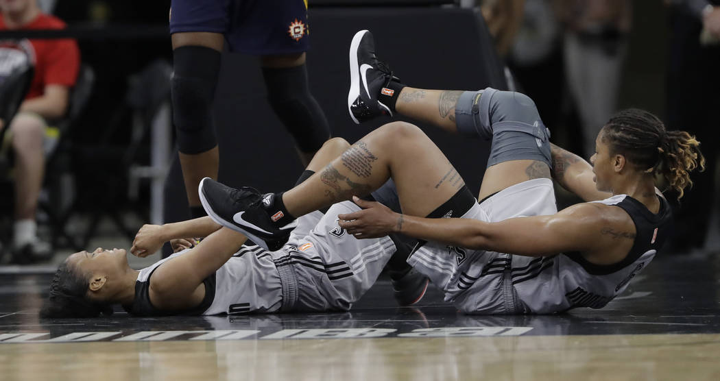 San Antonio Stars guard Moriah Jefferson, left, and teammate Alex Montgomery, right, lie on the court after the collided during the first half of a WNBA basketball game against the Connecticut Sun ...