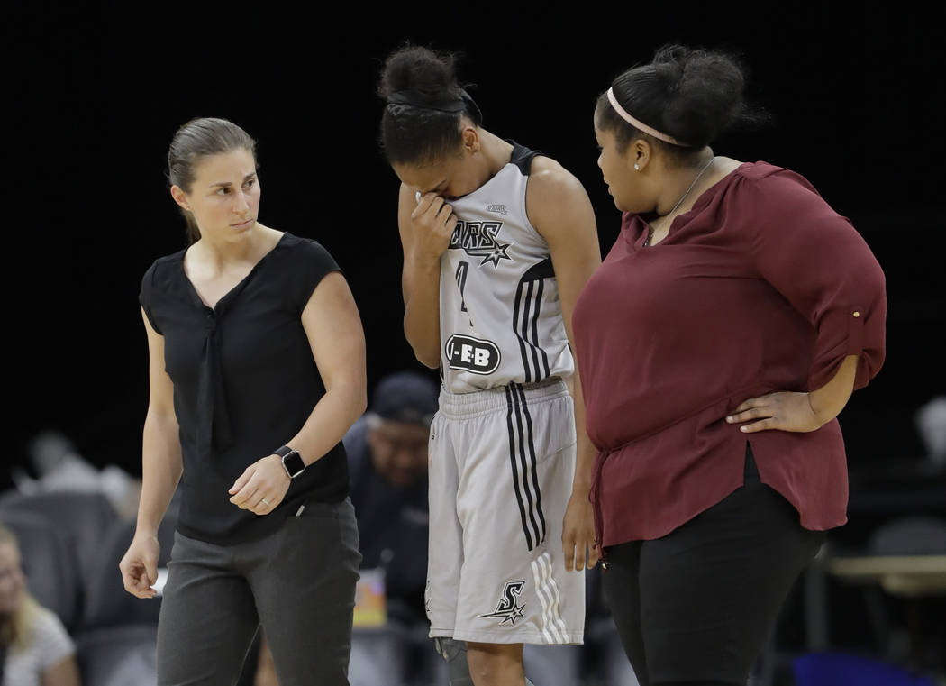 San Antonio Stars guard Moriah Jefferson, center is walked off the court after she collided during the first half of a WNBA basketball game against the Connecticut Sun, Wednesday, July 5, 2017, in ...