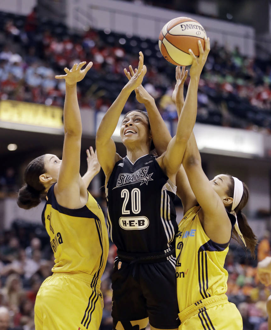 San Antonio Stars' Isabelle Harrison (20) puts up a shot against Indiana Fever's Natalie Achonwa, left, and Erica McCall during the first half of a WNBA basketball game, Wednesday, July 12, 2017,  ...