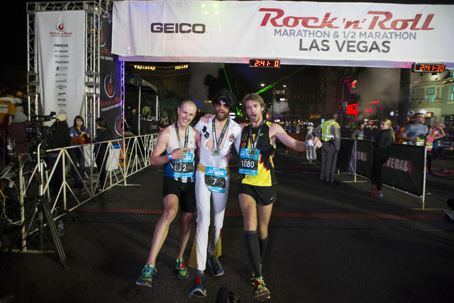 Top three runners from left,  Chip O'hara, who finished third, Michael Wardian, who finished first, and Eric Fitzpatrick who finished second, pose after the Rock-n-Roll Marathon at the Strip near  ...