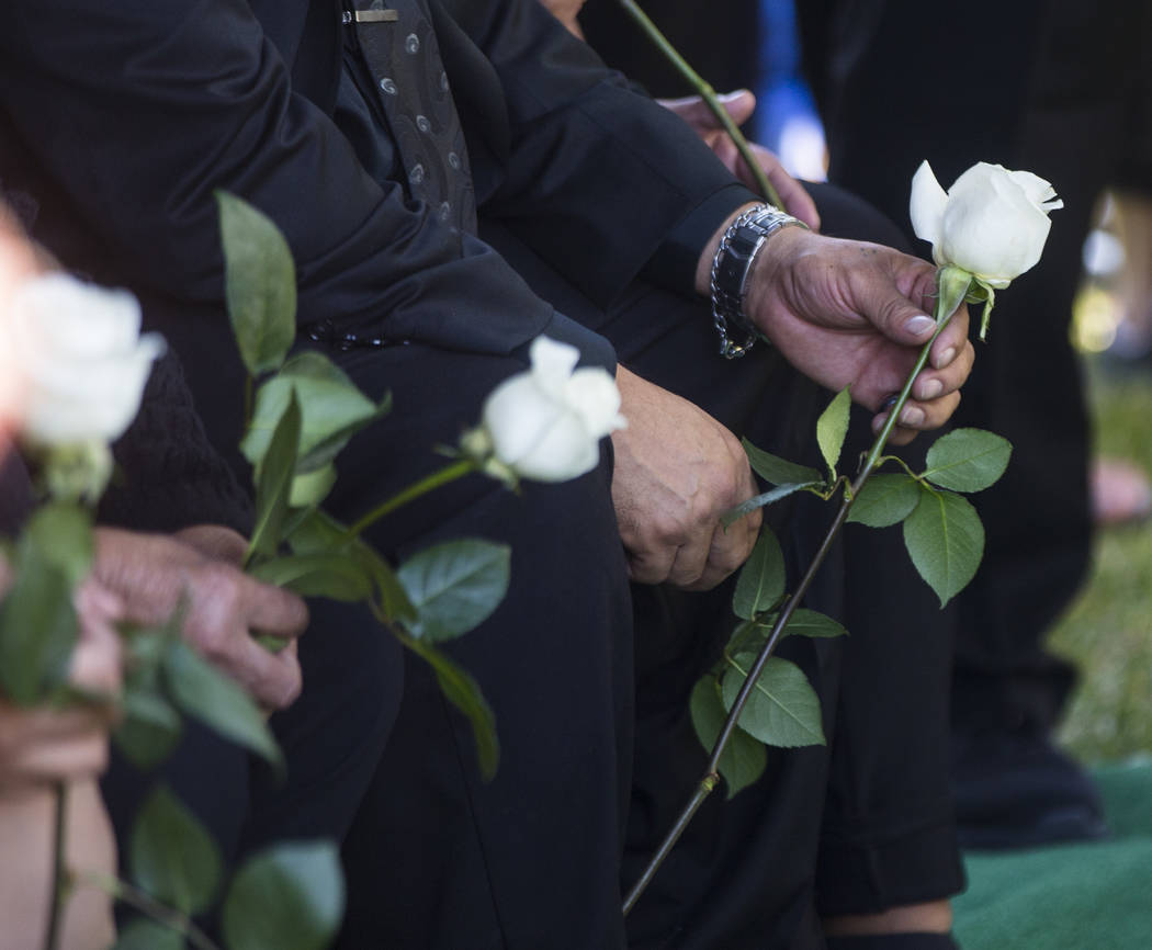 Gregorio De La Rosa, stepfather of Erick Silva, holds a rose during funeral services for Silva at Davis Funeral Home & Memorial Park in Las Vegas on Thursday, Oct. 12, 2017. Silva was working  ...