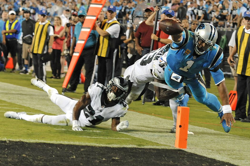 Carolina Panthers' Cam Newton (1) dives for the end zone as Philadelphia Eagles' Patrick Robinson (21) and Rodney McLeod (23) defend in the second half of an NFL football game in Charlotte, N.C.,  ...