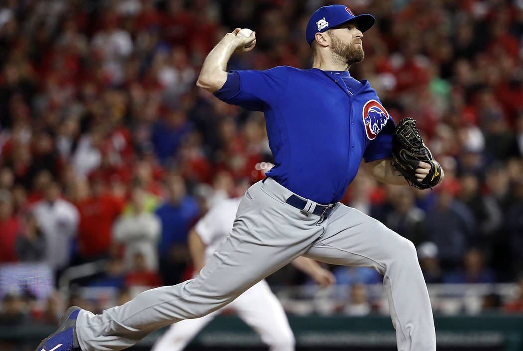 Chicago Cubs relief pitcher Wade Davis throws during the eighth inning in Game 5 of baseball's National League Division Series against the Washington Nationals, at Nationals Park, early Friday, Oc ...
