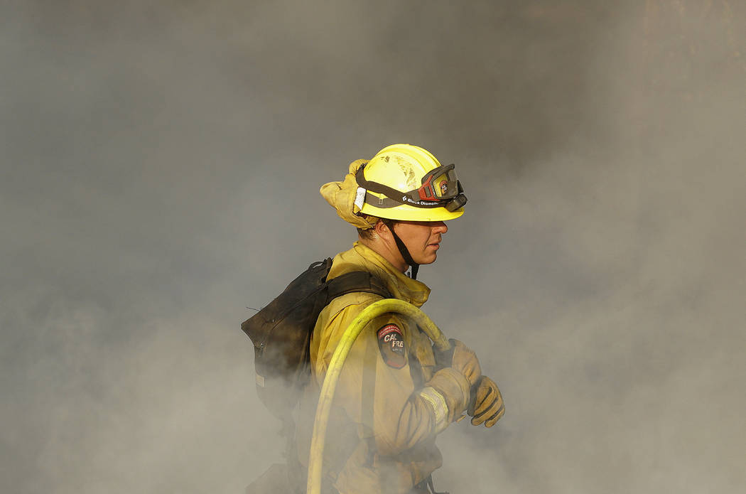 A Cal Fire firefighter works on hot spots on a hill in the Oakmont area of Santa Rosa, Calif., Thursday, Oct. 12, 2017. Gusting winds and dry air forecast for Thursday could drive the next wave of ...