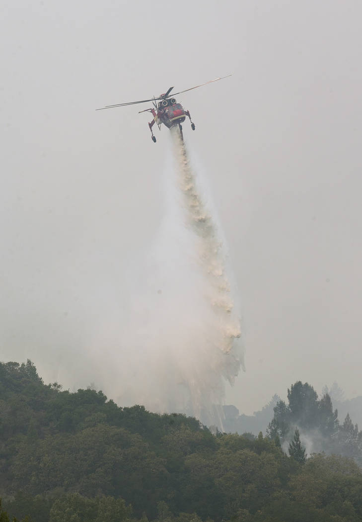 A helicopter drops a load of water on a wildfire Thursday, Oct. 12, 2017, in Sonoma, Calif. Gusting winds and dry air forecast for Thursday could drive the next wave of devastating wildfires that  ...