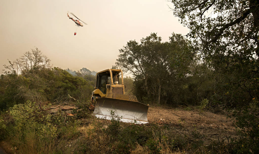 A bulldozer is used to cut a fire break as a helicopter flies over with a bucket of water to fight the flames of a massive wildfire Thursday, Oct. 12, 2017, in Sonoma, Calif. Gusting winds and dry ...