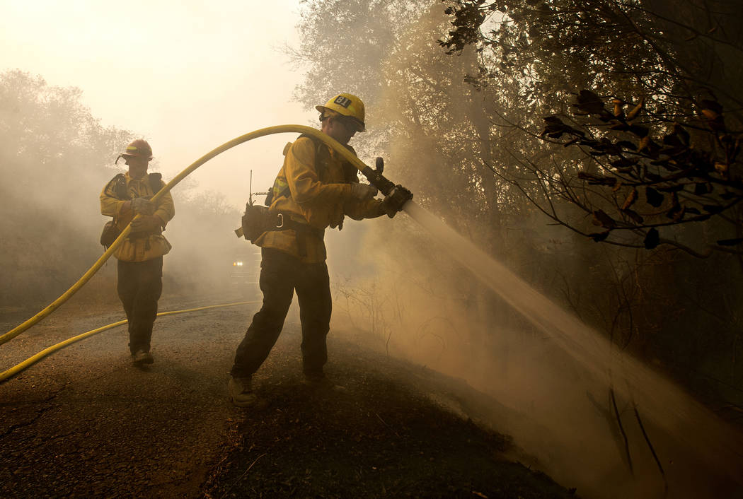 Santa Paula firefighter Tyler Zeller, right, hoses down a hot spot with the help of Jesse Phillips, Thursday, Oct. 12, 2017, in Sonoma, Calif. Firefighters from across the state have been brought  ...