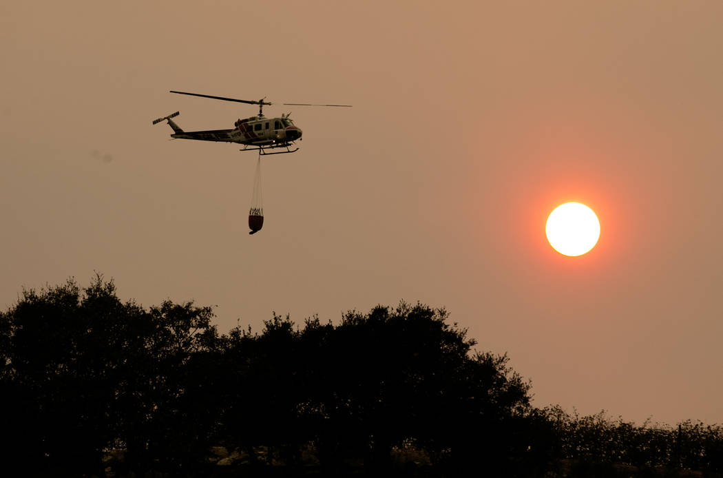 A helicopter flies through the smokey sky to drop a load of water on a wildfire Thursday, Oct. 12, 2017, in Sonoma, Calif. Officials say progress is being made in some of the largest wildfires bur ...