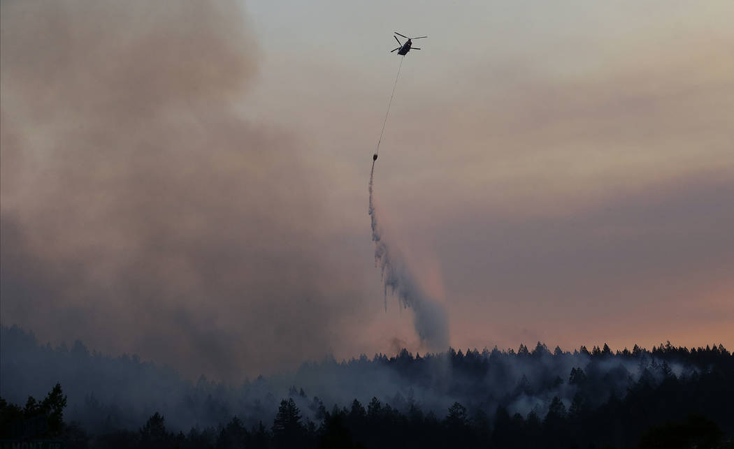 A helicopter drops water on a hill in the Oakmont area in Santa Rosa, Calif., Thursday, Oct. 12, 2017. A forecast for gusty winds and dry air threatened to fan the fires, which were fast becoming  ...