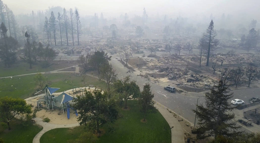 FILE - This Tuesday, Oct. 10, 2017, aerial image shows homes that were destroyed by a wildfire next to a playground in Santa Rosa, Calif. With winds expected to continue blowing smoke from the fir ...