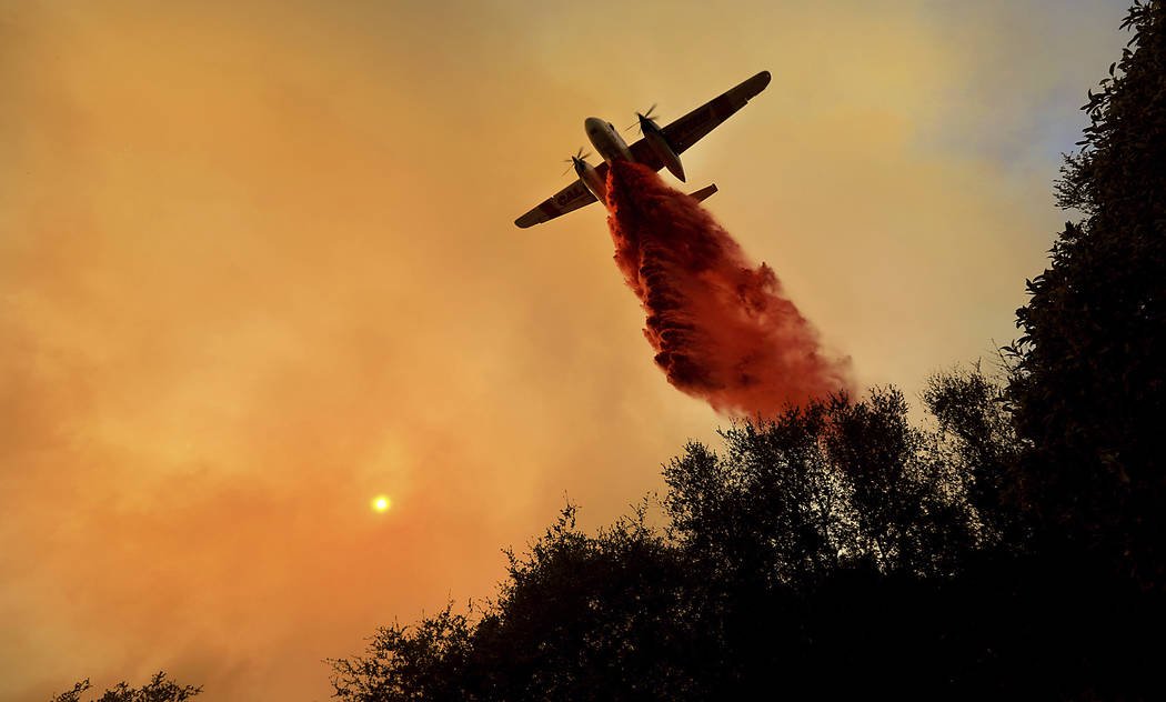 A Cal Fire air taker makes a drop on a wildfire as the pilot protects structures on the Hawkeye Ranch above Geyserville, Thursday Oct. 12, 2017. Thousands of firefighters are battling the blazes a ...