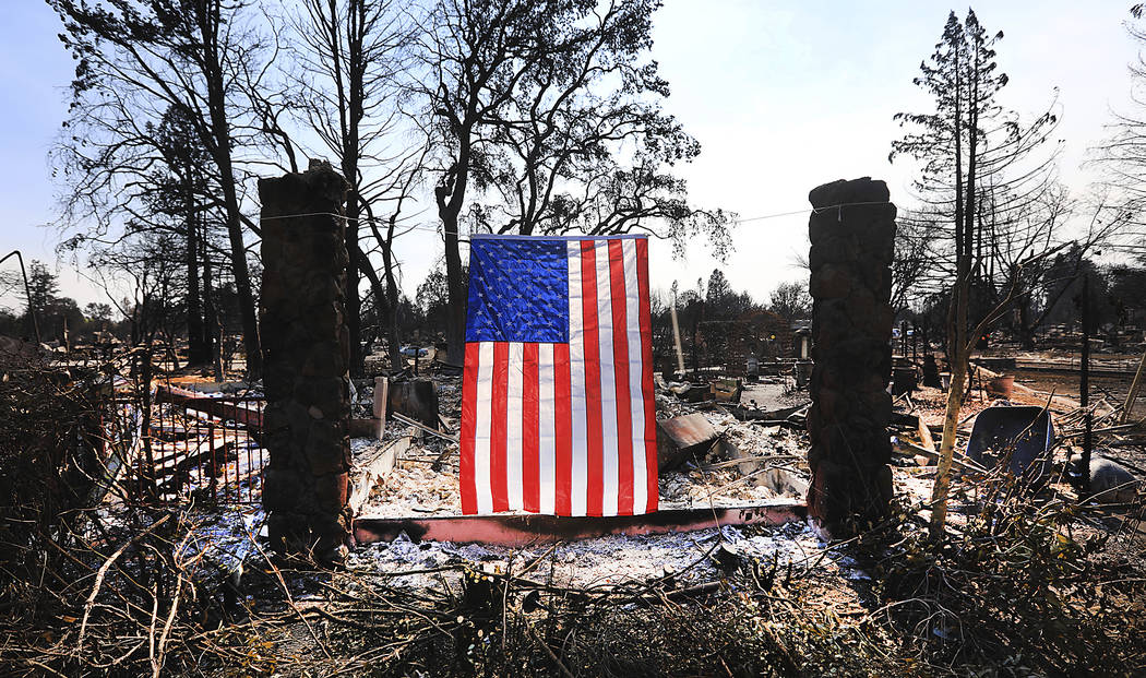 On Willowview Court in Santa Rosa, Calif., a homeowner displays an American flag amidst the destruction from a wildfire, Thursday Oct. 12, 2017. Since igniting Sunday in spots across eight countie ...