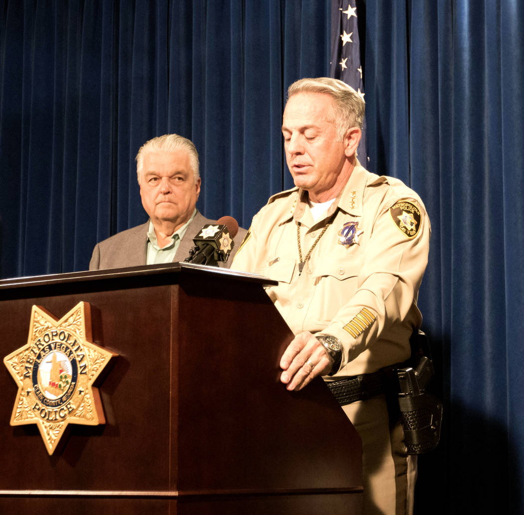 Clark County Commission Chairman Steve Sisolak, left, with Metropolitan Police Department Sheriff Joe Lombardo, center, as he addresses the media at a news briefing in Las Vegas, Friday, Oct. 13,  ...