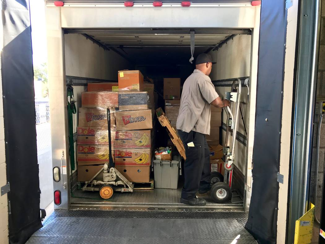 Reggie Cummings readjusts the boxes of rescued food in the back of his truck. By the end of his route, he'll have visited between 10-12 stores and filled the truck with groceries that would have o ...