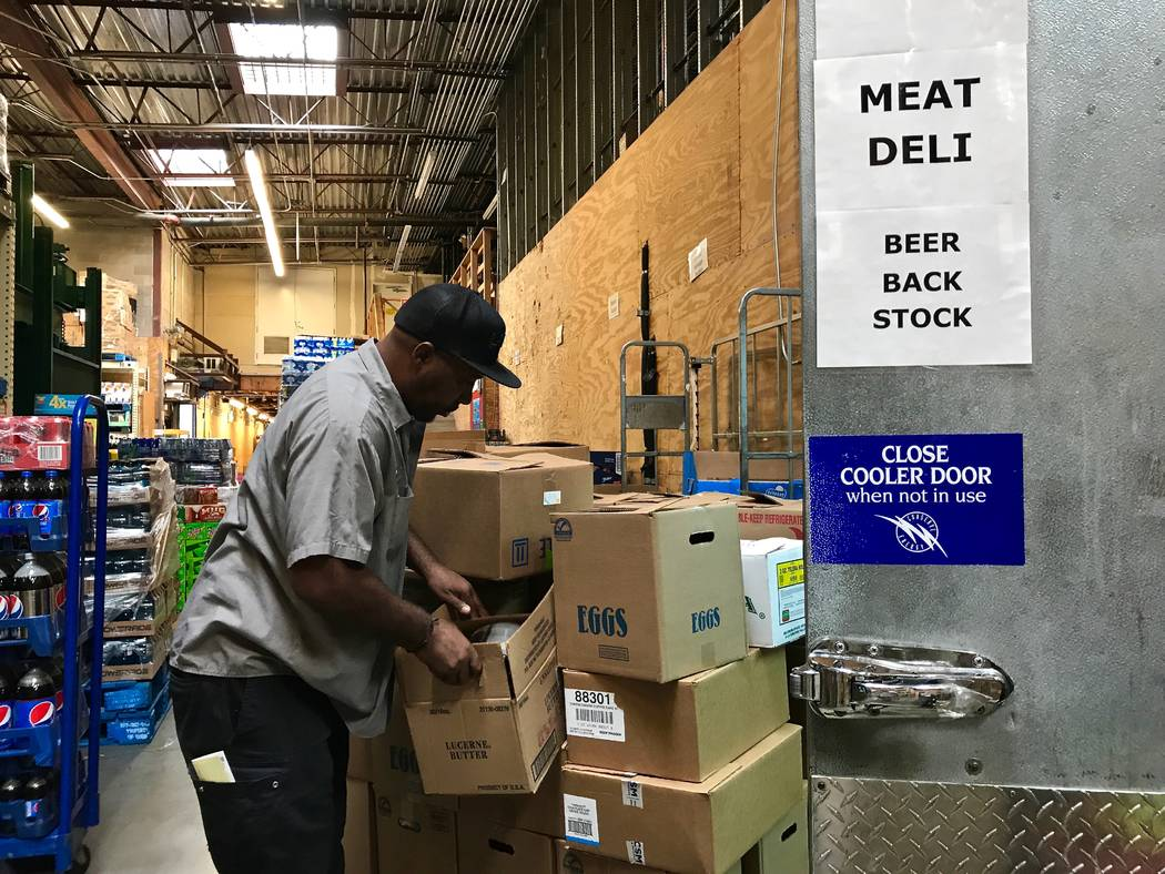 "Three Square truck driver Reggie Cummings loads ""rescued"" groceries onto his truck. The food, which is either close to code, mislabeled or otherwise undesirable, will eventually become meals for f ..."