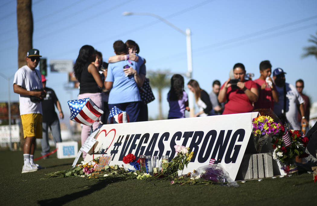 """People visit a makeshift memorial for victims of Sunday's mass shooting near the """"Welcome to Fabulous Las Vegas"""" sign in Las Vegas on Saturday, Oct. 7, 2017. Chase Stevens Las Ve ..."""