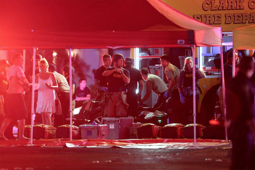 Medics treat the wounded as Las Vegas police respond during an active shooter situation on the Las Vegas Strip in Las Vegas on Sunday, Oct. 1, 2017. (Chase Stevens/Las Vegas Review-Journal) @csste ...