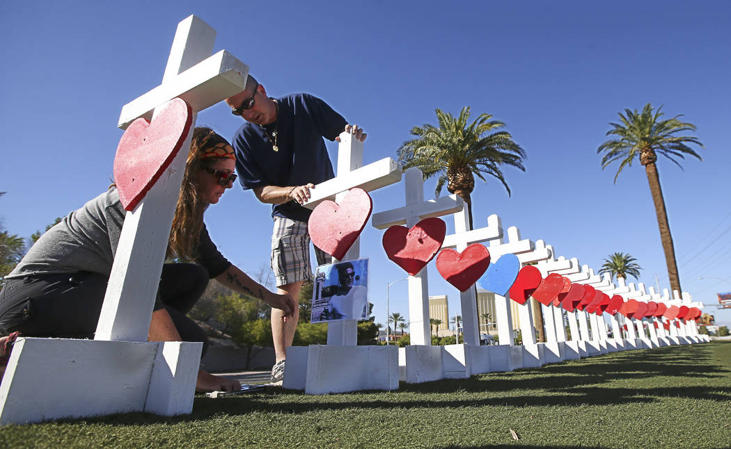 "Sherri Camperchioli, left, and Jordan Cassel place photos of victims of Sunday's mass shooting on crosses left in their memory near the ""Welcome to Fabulous Las Vegas"" sign in La ..."