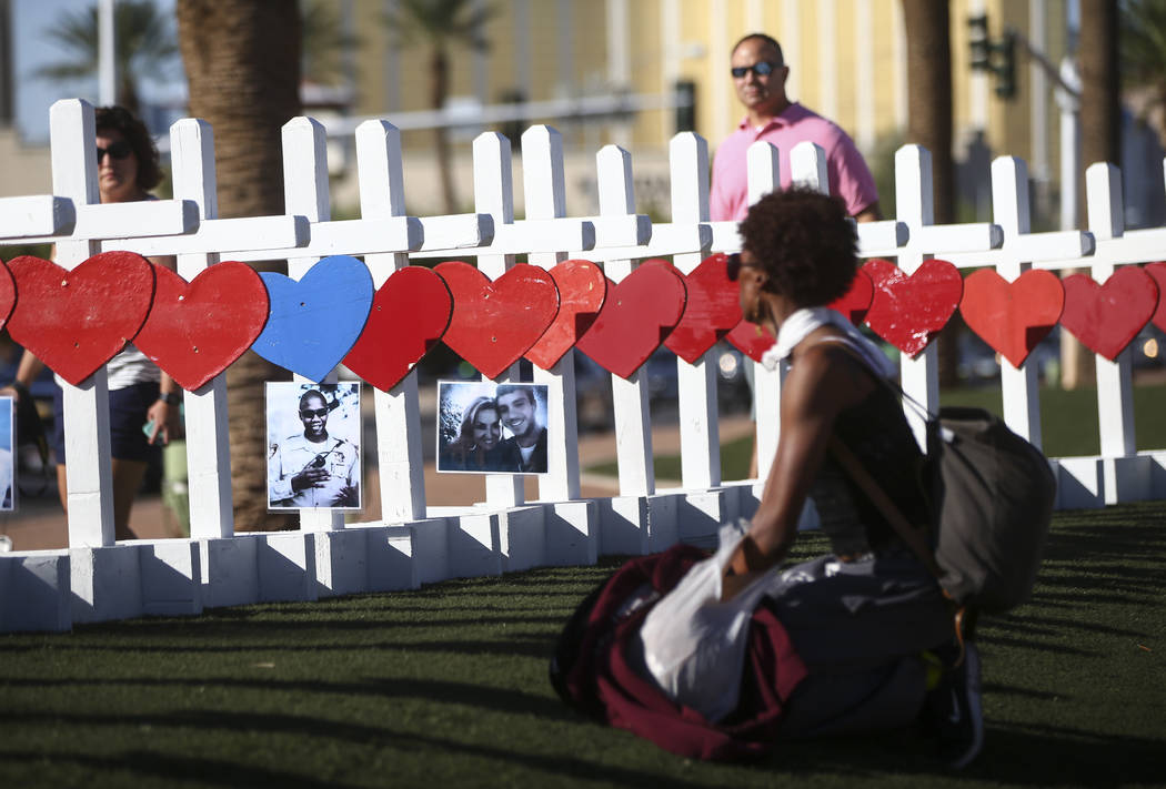"People look at crosses for the victims of Sunday's mass shooting placed near the ""Welcome to Fabulous Las Vegas"" sign in Las Vegas on Thursday, Oct. 5, 2017. Chase Stevens Las Ve ..."