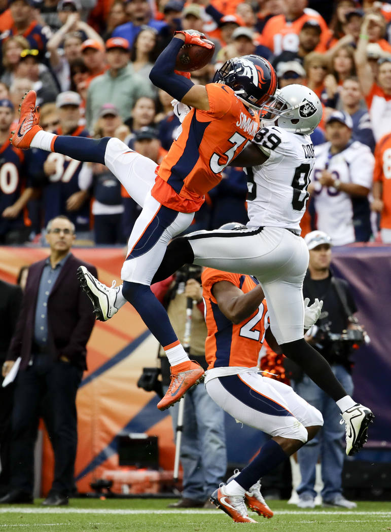 Denver Broncos strong safety Justin Simmons, left, intercepts a pass intended for Oakland Raiders wide receiver Amari Cooper during the second half of an NFL football game Sunday, Oct. 1, 2017, in ...