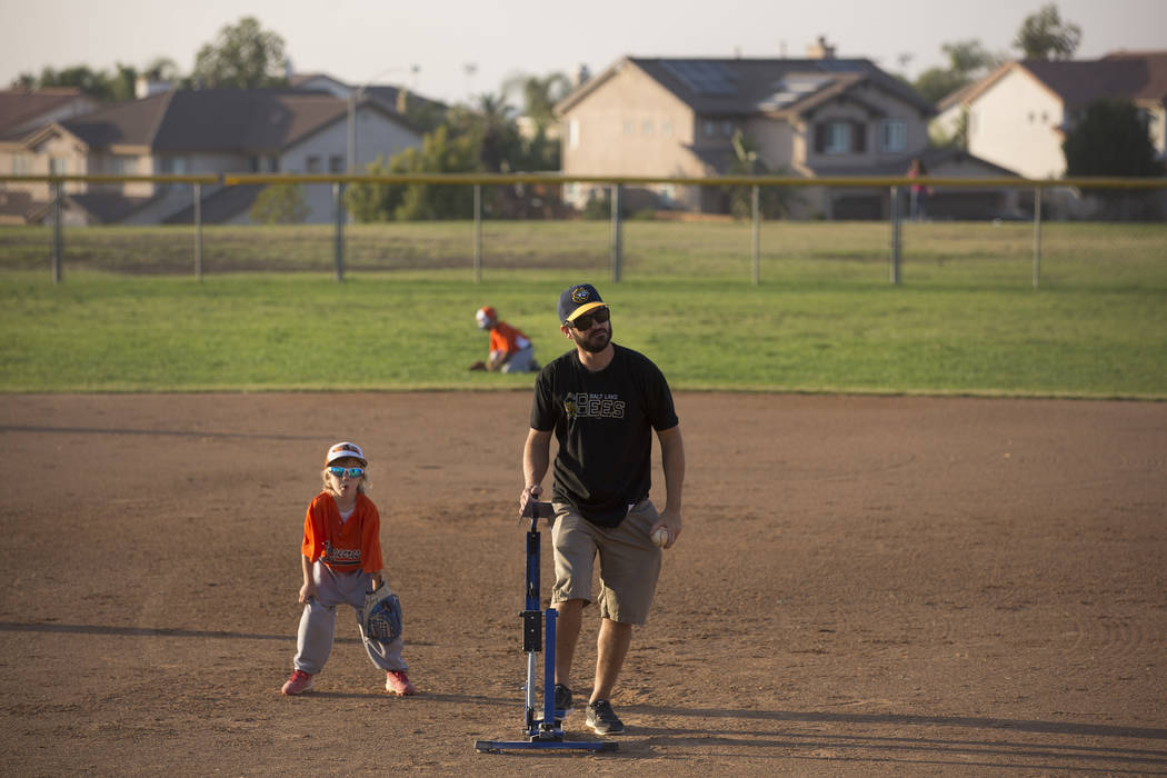 Dylan Bertino helps pitch his son's baseball game, a team which he coaches, at Orange Terrace Community Park in Riverside, California on Friday, Oct. 13, 2017. Bertino was at Route 91 on Oct. 1 wh ...