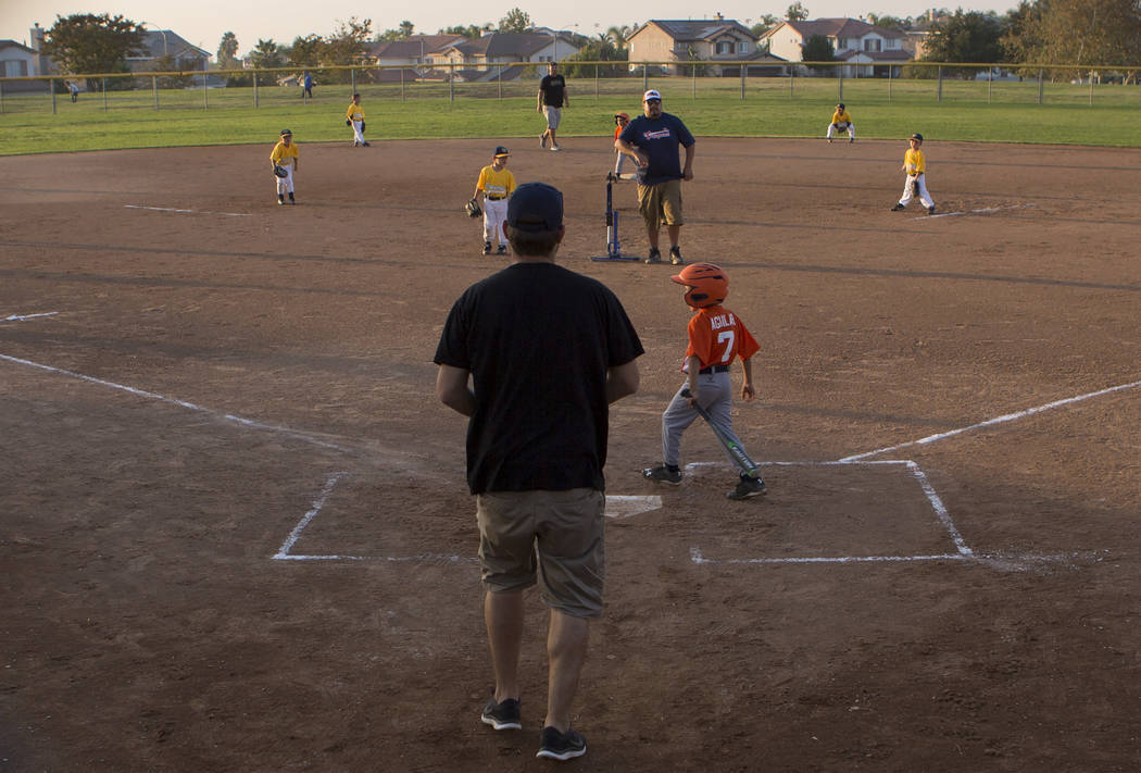 Dylan Bertino, center, coaches his son's baseball game at Orange Terrace Community Park in Riverside, California on Friday, Oct. 13, 2017. Bertino was at Route 91 on Oct. 1 when a man opened fire, ...