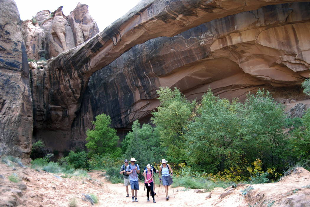 People walk near Morning Glory Arch near Moab, Utah, in Negro Bill Canyon. (Brian Maffly /The Salt Lake Tribune via AP)