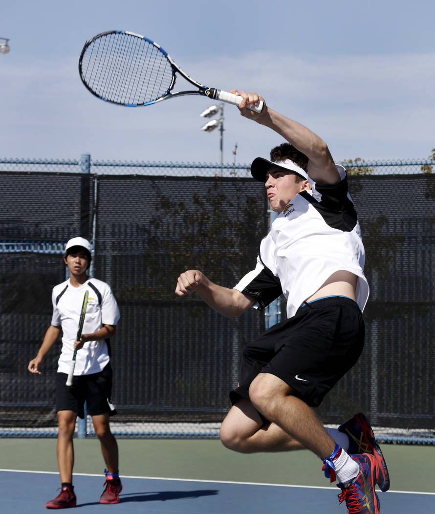 Clark High's doubles player Teo Tabar returns the ball against Palo Verde High as his tennis partner Dustin Mader, right, looks on during the Class 4A state finals at Darling Tennis Center Friday, ...