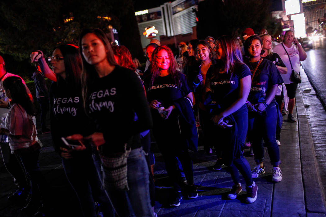 People walk along the Strip during the Vegas Strong Las Vegas Strip Walk honoring the victims of the Route 91 Harvest Festival shooting in Las Vegas, Sunday, Oct. 15, 2017. Joel Angel Juarez Las V ...