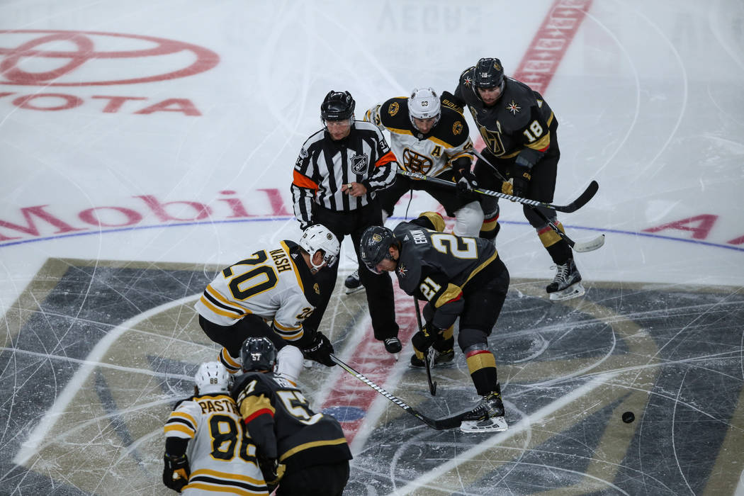 Boston Bruins center Riley Nash (20), left, and Vegas Golden Knights center Cody Eakin (21), right, face off during the puck drop for the first period of an NHL hockey game at T-Mobile Arena in La ...