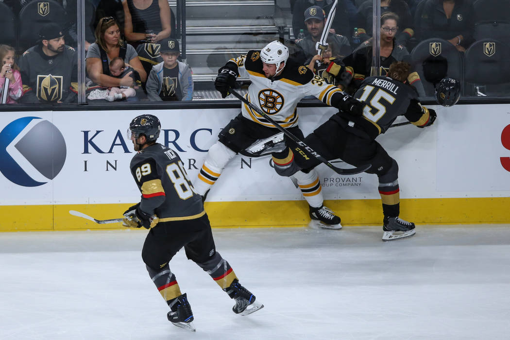 Boston Bruins left wing Matt Beleskey (39), center, knocks the helmet off Vegas Golden Knights defenseman Jon Merrill (15), right, during the first period of an NHL hockey game at T-Mobile Arena i ...