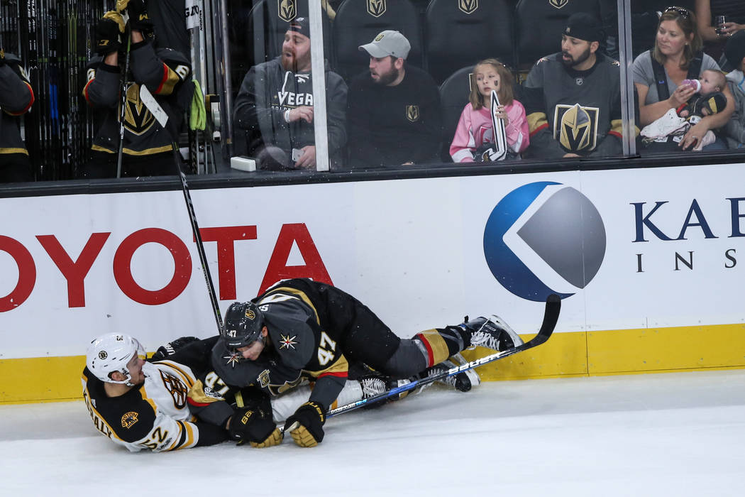 Boston Bruins center Sean Kuraly (52), left, is knocked down by Vegas Golden Knights defenseman Luca Sbisa (47), right, during the first period of an NHL hockey game at T-Mobile Arena in Las Vegas ...