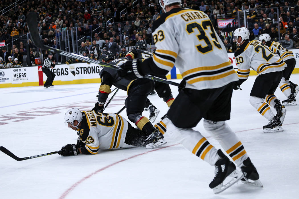 Boston Bruins left wing Brad Marchand (63), left, lays on the ground after falling against the Vegas Golden Knights during the second period of an NHL hockey game at T-Mobile Arena in Las Vegas, S ...