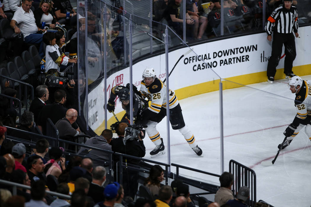 Vegas Golden Knights left wing Pierre-Edouard Bellemare (41), left, and Boston Bruins defenseman Brandon Carlo (25), right, fight over the puck during the third period of an NHL hockey game at T-M ...