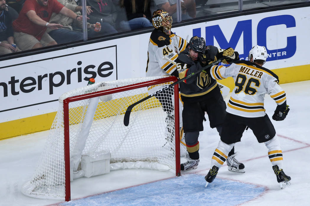 Vegas Golden Knights left wing David Perron (57), center, is punched by Boston Bruins defenseman Kevan Miller (86), right, during the third period of an NHL hockey game at T-Mobile Arena in Las Ve ...